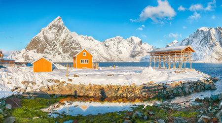 Breathtaking winter view of Sakrisoy village and snowy mountaines on background. Popular tourist destination on Lofotens. Location: Sakrisoy, Moskenesoya, Lofoten; Norway, Europe