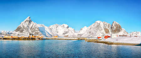 Beathtaking winter view of Sakrisoy village and snowy mountaines on background. Popular tourist destination on Lofotens. Location: Sakrisoy, Moskenesoya, Lofoten; Norway, Europe