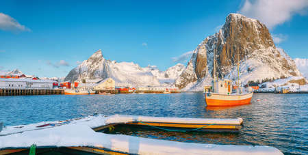 Fabulous winter view on Hamnoy village with port and Festhaeltinden and Olstinden peaks on background. Location: Hamnoy, Moskenesoya, Lofoten; Norway, Europe Imagens