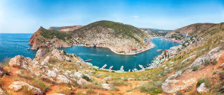 Panoramic view of Balaklava bay with yachts and ruines of Genoese fortress Chembalo in Sevastopol city from the height. Crimea