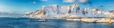 Fabulous winter view of Reine and Sakrisoya villages seen from Hamnoy and snowy mountaines in background. Location: Olenilsoya island, Lofoten; Norway, Europe
