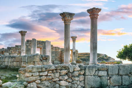 Fantastic sunset over ruins of the Basilica in ancient city Chersonese - national historical and archaeological reserve. Sevastopol. Crimea 免版税图像