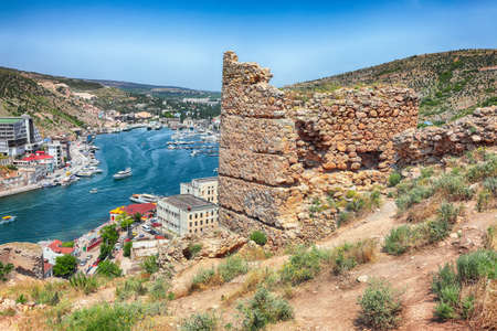 Scenic view of Balaklava bay with yachts and ruines of Genoese fortress Chembalo in Sevastopol city from the height. Crimea
