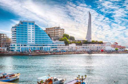 Residential complex Cape Khrustalny and the obelisk to the Hero City of Sevastopol during sunny day. Sevastopol embankment. Crimea