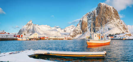 Fabulous winter view on Hamnoy village with port and Festhaeltinden and Olstinden peaks on background. Location: Hamnoy, Moskenesoya, Lofoten; Norway, Europe 免版税图像