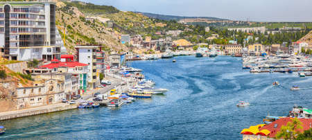 View of Balaklava bay with yachts from the Genoese fortress Chembalo in Sevastopol city. Yachts and boats moored to the shore of Balaklava. Crimea 免版税图像