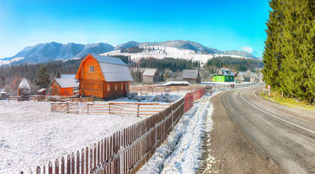 Fantastic winter landscape with wooden houses in snowy mountains. First snow in mountains. Location: Carpathian Mountains, Ukraine, Europe
