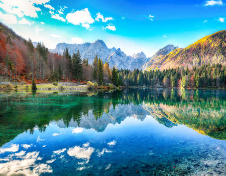 Fairytale view of Fusine lake with Mangart peak on background. Popular travel destination of Julian Alps. Location: Tarvisio comune, Province of Udine, Italy, Europe