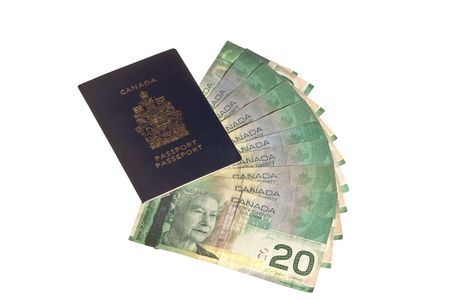 Canadian passport with canadian money (twenty dollar bills) isolated on white background.