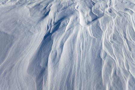 wind created patterns on surface of packed snow
