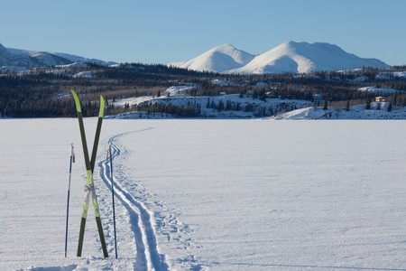 Cross country skiing. Skis and poles near ski track on frozen lake. Perfect winter snow conditions with blue sky. Stock Photo