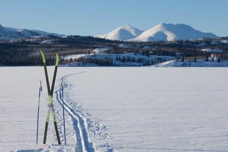 Langlaufen. Skier und St�cke in der N�he von Ski verfolgen zugefrorenen See. Perfekte Winter Schneebedingungen mit blauem Himmel.