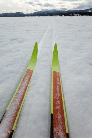 Cross country skiing. Skis in tracks on frozen lake with distant shoreline. Perfect winter snow conditions. photo