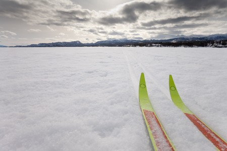 distant: Cross country skiing. Skis in tracks on frozen lake with distant shoreline. Perfect winter snow conditions.