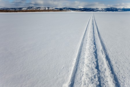 frozen lake: Snowmobile track in snow on surface of frozen lake leading to distant shore on sunny winter day.