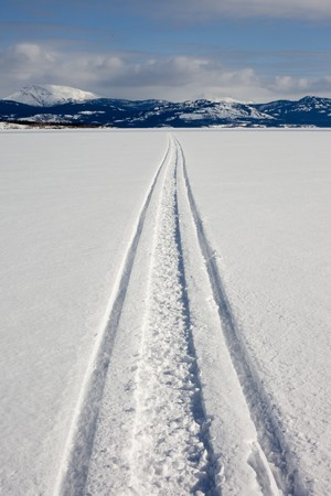 Snowmobile track in snow on surface of frozen lake leading to distant shore on sunny winter day. Stock Photo - 7281552