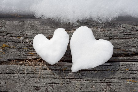 frigid: Two Valentines Day Hearts formed from snow on weathered timber surface.