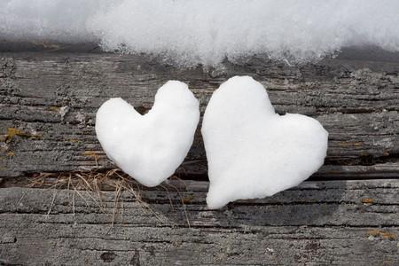 Zwei Valentinstag Herzen aus Schnee auf Fl�che verwittertem Holz gebildet.