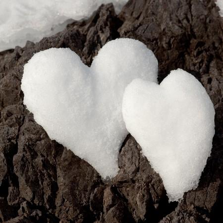 Twee Valentijnsdag Hearts gevormd uit sneeuw op rock oppervlak.  Stockfoto