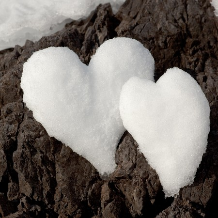 romance: Two Valentines Day Hearts formed from snow on rock surface.