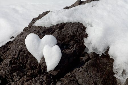 Two Valentine's Day Hearts formed from snow on rock surface. Stock Photo - 7281538