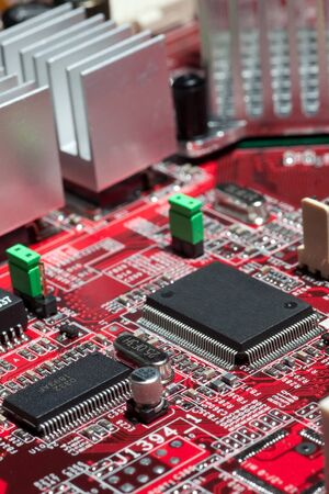 microelectronics: Red circuit board with electronic components such as microchips, condensors, resistors, and transistors. Stock Photo