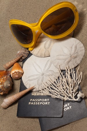 glasses in the sand: Close-Up of passports, sun glasses, sand dollars (Echinoderm), coral and shells: Beach Vacation Concept