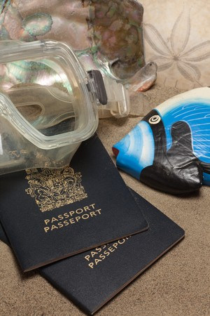 Close-Up of passports, diving mask, sand dollar (Echinoderm), coral fish and abalone:  Beach Vacation Concept