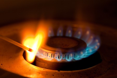 stove: Blue flames of propane burner ignite match Stock Photo