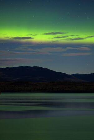 aurora borealis: Intense Aurora borealis showing between clouds during moon lit night being mirrored on Lake Laberge, Yukon T., Canada.