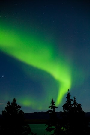 Intense Aurora borealis in maan aangestoken nachthemel worden gespiegeld op oppervlakte van het meer.