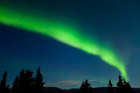 Intense Aurora borealis and lots of stars in moon lit night sky. photo
