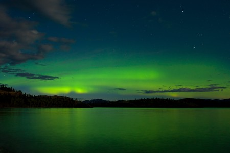 Intense Aurora borealis in moon lit night being mirrored on Lake Laberge, Yukon T., Canada. Stock Photo