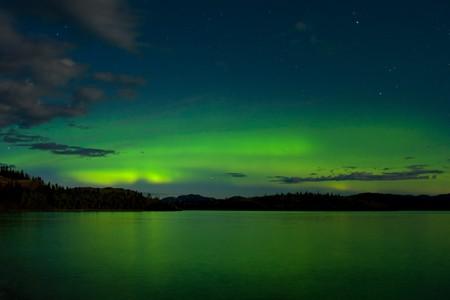 Intensive Aurora Borealis in Leuchten Mond Nacht gespiegelte am Lake Laberge, Yukon t., Kanada.
