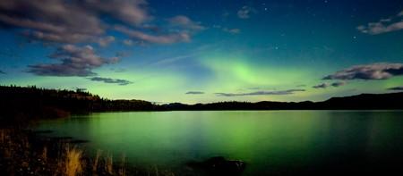 Borealis intenso de Aurora en noche de Luna iluminado que se refleja en el lago Laberge, T. de Yukón, Canadá.
