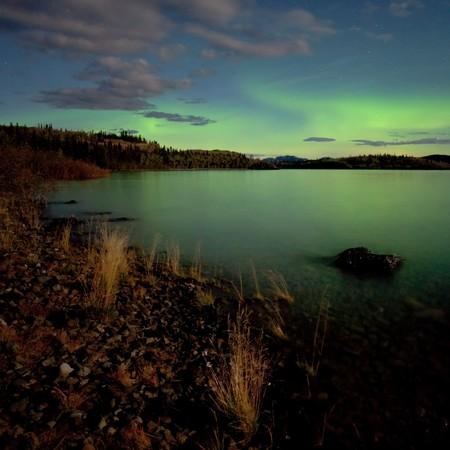 Intense Aurora borealis in moon lit night being mirrored on Lake Laberge, Yukon T., Canada. photo