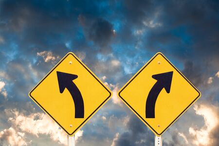 Confusing road signs: left or right curve? with dramatic sky background Stock Photo - 7908509