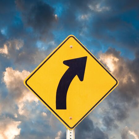 Road sign warning of dangerous curve with dramatic sky background. Stock Photo - 7908491