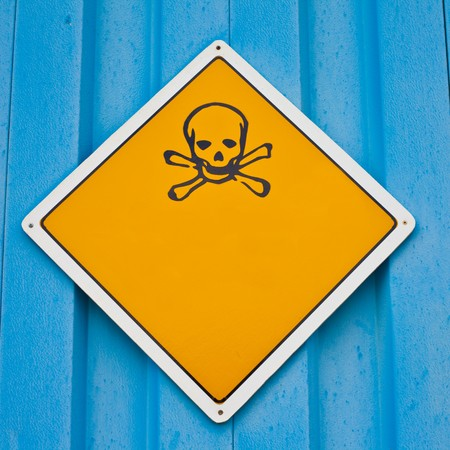 Skull and crossbones warning sign on blue background white with lots of copyspace for your message. photo