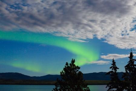 ionosphere: Intense Aurora borealis showing between clouds during moon lit night over Lake Laberge, Yukon T., Canada.