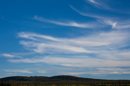 cirrus: Cirrus clouds over forested hills. Stock Photo