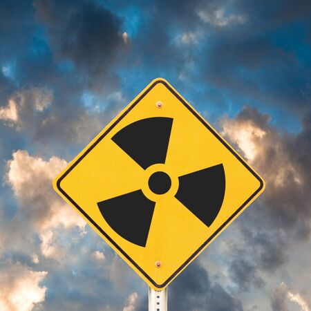 sky  dramatic: Road sign with radioactivity warning symbol on it with dramatic sky background. Stock Photo