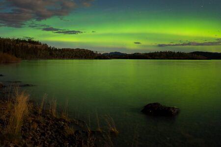polar light: Borealis intenso de Aurora en noche de Luna iluminado que se refleja en el lago Laberge, T. de Yuk�n, Canad�.