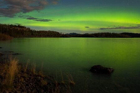 northern light: Intense Aurora borealis in moon lit night being mirrored on Lake Laberge, Yukon T., Canada. Stock Photo