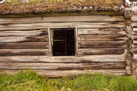 Historic log house, wall with glassless window frame and earth roof. Stock Photo
