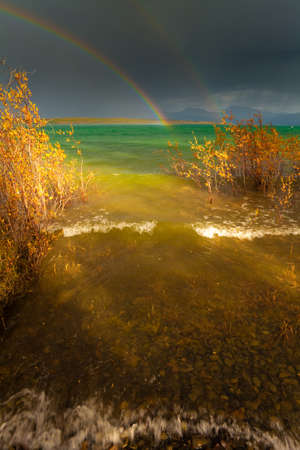 thundershower: A Thundershower producing a rainbow over the gree-blue waters of pristine Lake Laberge, Yukon Territory, Canada. Stock Photo