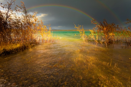 A Thundershower producing a rainbow over the gree-blue waters of pristine Lake Laberge, Yukon Territory, Canada. Stok Fotoğraf