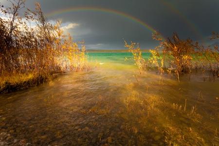 Ein Gewitterschauer produzieren einen Regenbogen �ber dem gr�n-blaue Wasser des unber�hrten Lake Laberge, Territorium Yukon, Kanada.