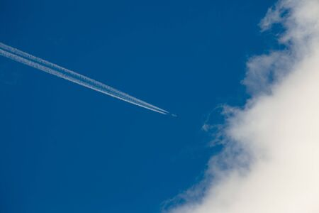 enters: Aircraft leaving vapor trail on blue sky enters white cloud. Stock Photo