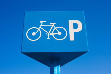 Blue parking bicycle sign on blue sky background. photo